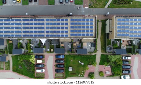 Aerial photo of newly built apartment complex with photovoltaic solar panels installed they absorb sunlight as source of energy to generate electricity in this residential application