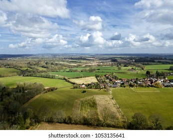 Aerial photo over rural English village surrounded by green countryside