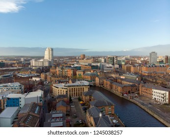 Aerial photo overlooking the Leeds City Center taken on a beautiful part cloudy day in West Yorkshire UK showing the Leeds and Liverpool canal high rise buildings and local businesses and hotels.