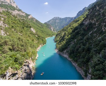 Aerial photo of People have a rest in the gorge Verdon on a catamarans, boats and paddles, lake Cross, azure water of the river, the rocky coast with trees