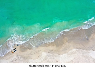 Aerial Photo of People Standing on the Beach of Anna Maria Island with the Ocean Surf Coming Ashore.