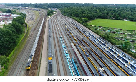 Aerial photo of railroad hub or railway terminal showing trains passing by also showing different trains parked next to each other on the rail tracks