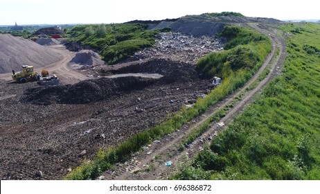 Aerial photo of road of garbage disposal site showing municipal solid waste and rubbish piled up on hill and ready for recycling and converting waste materials into new materials and objects