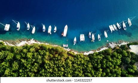 Aerial photo of sail boats and yachts docked in traditional fishing village of Fiskardo, Kefalonia island, Ionian, Greece