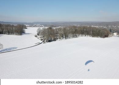 Photo aérienne de Saint-Cyr-sous-Dourdan sous la neige, avec l'ombre d'un parapente motorisé, le 8 février 2018, département de l'Essonne, région Île-de-France, France
