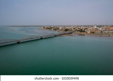 Aerial photo of Senegal river in Sant Louis, Senegal, with the Faidherbe bridge seen connecting the new part of the city on an overcast day.
