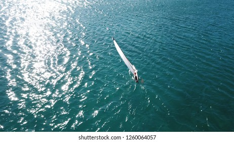 Aerial photo of small scale model handmade wooden Remote Controlled Sail boat in competition at calm emerald sea