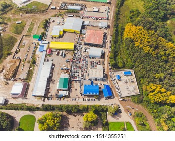 Aerial photo of small temporary car lot to store new cars for resale and car dealers who do not have free space for storage high altitude top down view.