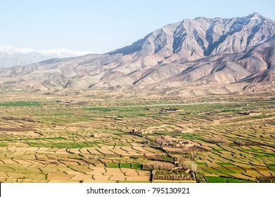 Aerial photo of small villages between Ghazni and Kabul in Afghanistan in a large agricultural valley with green fields and mountains