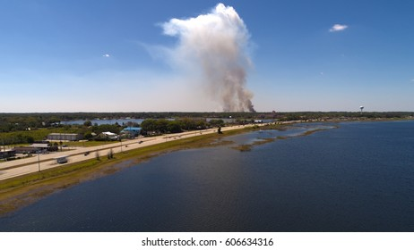 Aerial photo of smoke from a distant brush fire. In front of the smoke is a busy street with motion blurred cars next to a lake in a small town.