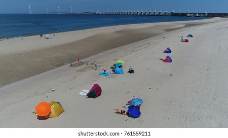 Aerial photo summertime beach showing people recreating on sand using colorful parasols beach towels in background showing Oosterscheldekering Eastern Scheldt storm surge barrier part of Delta Works