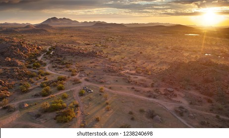 Aerial photo of sunrise over rocky desert, long shadows and beautiful colors. Three offroad cars in vaste wilderness, morning near Spreetshoogte Pass, Nauchas, Namibia.