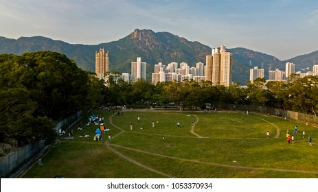 Aerial photo of sunset in Hong Kong with the Lion Rock hill-line on background with a park on the hill on foreground