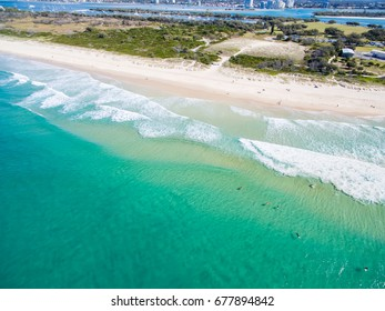 An aerial photo of Surfers waiting for a wave in clear blue water