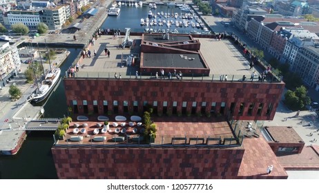 Aerial photo tall building roof in Belgium Antwerp located along the river Scheldt in Eilandje district showing people enjoying the beautiful weather of summer day