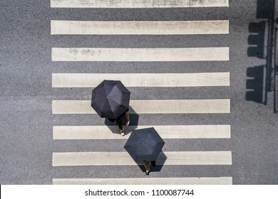 Aerial photo top view of people under umbrella walk on street in the city over pedestrian crossing traffic road