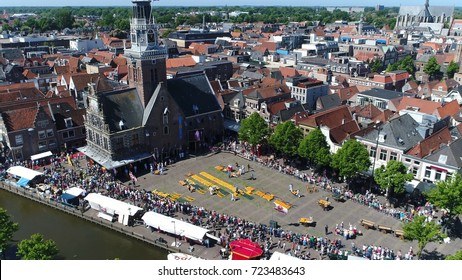 Aerial photo traditional cheese market located at Waagplein Alkmaar showing cheese merchants walking with trays of Alkmaar cheese towards the next buyer this is a popular tourist attraction in Holland