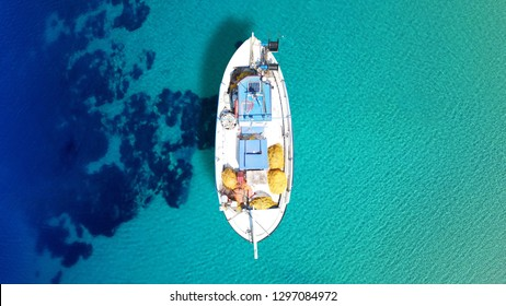 Aerial photo from traditional picturesque fishing boat on turquoise clear sea as seen from top in island of Paros, Cyclades, Greece