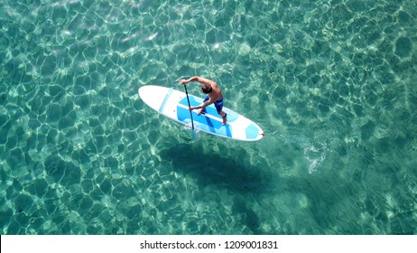 Aerial photo of unidentified man practicing stand up paddle board or SUP in tropical exotic turquoise calm sea sandy beach
