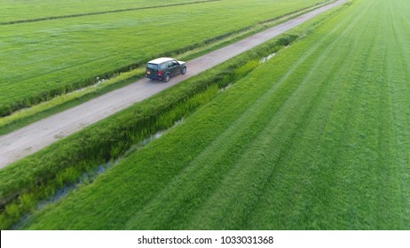 Aerial photo of unpaved road and off road vehicle following the all wheel car rural area drone view flight backwards away from the SUV beautiful nature and outdoors area typical offroad SUV scene