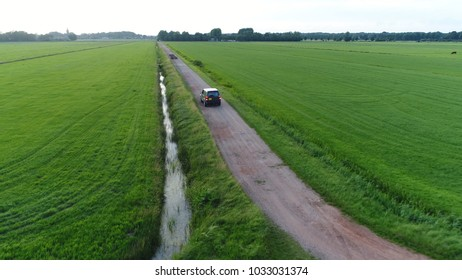 Aerial photo of unpaved road and off road vehicle braking and backing up rural area drone view flight backwards away from the SUV beautiful nature and outdoors area typical offroad SUV scene