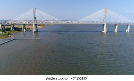 Aerial photo Vasco da Gama Bridge moving right in Portuguese Ponte Vasco da Gama cable-stayed bridge flanked by viaducts and rangeviews that spans Tagus River in Lisbon the capital of Portugal