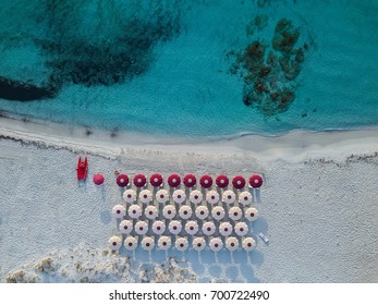 Aerial photo view of lifeguard boat and sun beds with umbrellas on Rena Bianca Beach in Sardinia Italy.