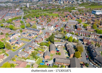 Aerial photo of the village of Beeston in Leeds West Yorkshire showing a typical British park along side rows of 1940's terrace houses, roads and streets, taken in the spring time
