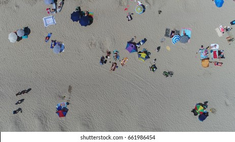 Aerial Photo Of White Sand Beach With People Sun Bathing Also Showing Parasols And Towels