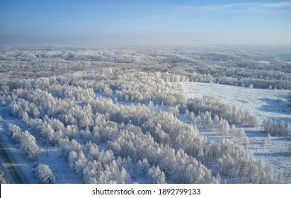 Aerial photo of winter road surrounded by birch forest. Drone shot of trees covered with hoarfrost and snow. Natural winter background.