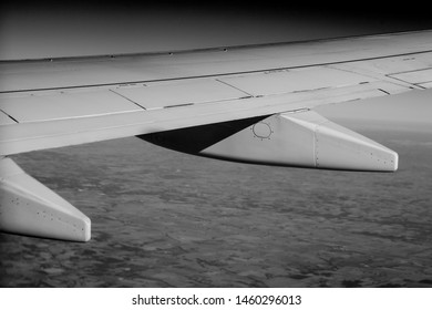 Aerial photograph of aircraft wing in black & white.