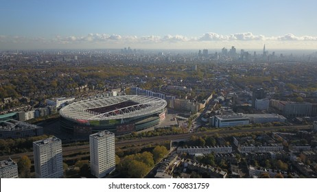 Aerial photograph (drone flight) of a large, major football stadium in the north of London, England with the london skyline visible on the horizon on a bright sunny day.