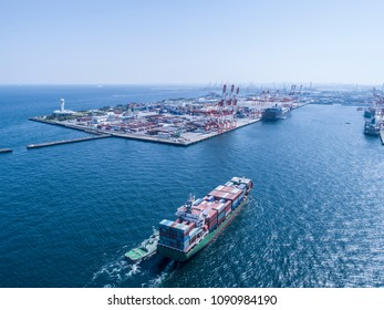 An aerial photograph of a large container ship towing a small ship. Cargo area.