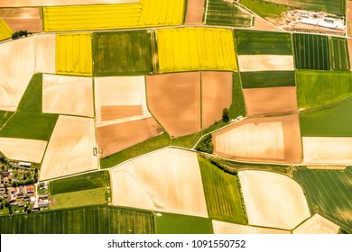 Aerial photograph of a patchwork of green and yellow farm fields and homes near Frankfurt Germany taken from a plane making a great travel or agricultural background.