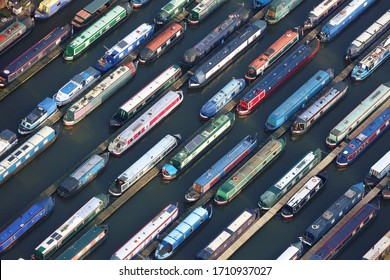 An aerial photograph taken from a helicopter of a large canal narrow boat marina in Britian. Many colourful pleasure boats are moored in lines making an interesting striped repeating pattern.