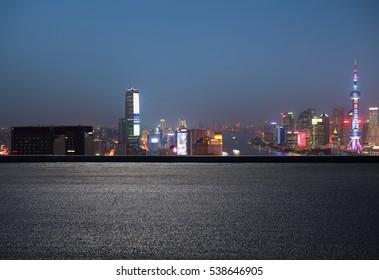 Aerial photography bird view at Empty road floor surface with city landmark buildings background at Shanghai bund Skyline of night scene
