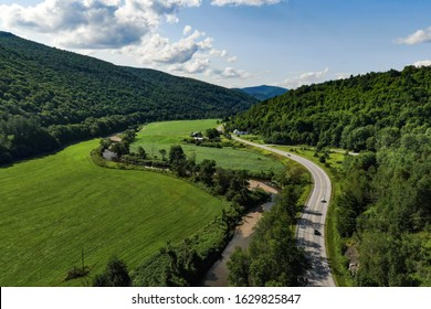 Aerial photography capturing the scenic route VT-100, guiding through Vermont. A historical road embraced by the green mountains and breathtaking spots made by mother nature.