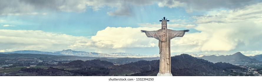 Aerial photography drone point of view Statue of Christ on a top of Monteagudo Castle fortress and mountain range surrounding countryside of Murcia, cloudy sky, cropped image, south-eastern Spain