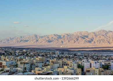 aerial photography of Eilat Israeli city on Red sea Gulf of Aqaba waterfront district, outdoor scenery landscape with picturesque sand stone desert mountain ridge in Jordan background