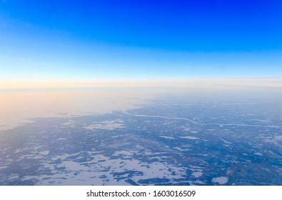 Aerial photography, frozen river in the soft morning light at dawn. The view from the airplane window on the snowy countryside of Finland. Winter landscape. Christmas in Lapland.
