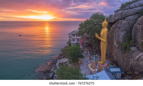 aerial photography in the morning at the golden buddha standing statue in Khao Takiab temple.beautiful sunshine above the Hua Hin ocean through to the golden Buddha landmark of Hua Hin