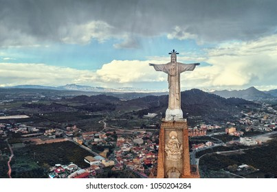 Aerial photography wide angle drone point view Statue of Christ on top of the limestone rock Monteagudo Castle fortress and cityscape of Murcia and surrounding countryside, south-eastern Spain