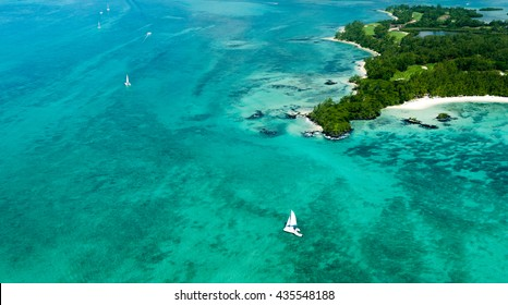 Aerial picture of the east coast of Mauritius Island. Beautiful lagoon of Mauritius Island shot from above. Catamaran boat sailing in turquoise lagoon