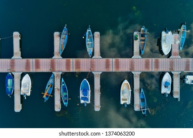 Aerial picture of floating dock with boats, motorboats and vessels floating on water in lake Small Prespes, Northern Greece