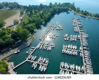Aerial picture of marina a dock with yachts and boats, motorboats and vessels floating on water in dock.