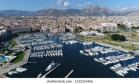 Aerial picture of marina yacht club located at Palermo Sicily Italy showing streets on left and harbor on right furthermore showing the city center and mountains in background