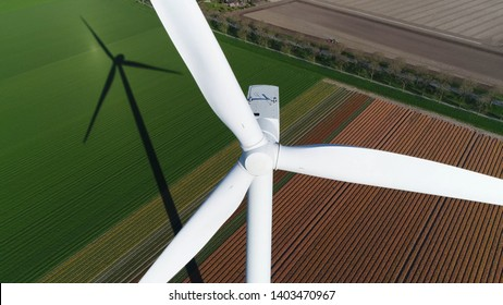 Aerial picture of wind turbine during sundown also showing the long shadow of mast of the energy converter is a device that converts the winds kinetic power into electrical electricity