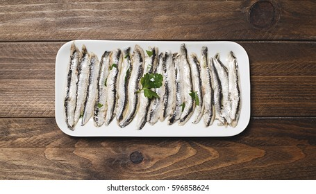 Aerial plane of anchovy dish with olive oil, vinegar and lemon. Horizontal shoot.