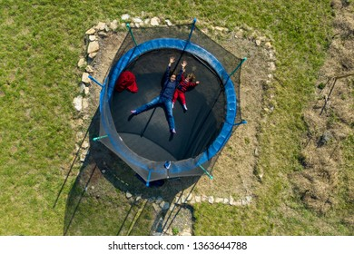 Aerial point of view of mother with her daughter having fun and jumping on trampoline by drone