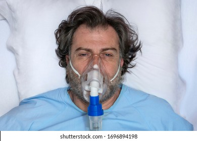 Aerial portrait of an elderly person, with oxygen mask, in a hospital bed